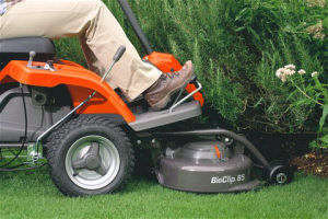 Husqvarna R112C rider lawn mower cutting under a bush