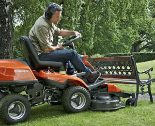 Husqvarna R112C rider lawn mower cutting under a bench