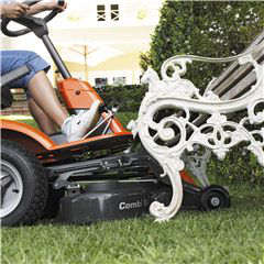 Husqvarna rider lawnmower R214T cutting grass under a bench